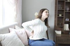 Mooie jonge vrouw die aan rugpijn thuis lijden royalty-vrije stock afbeeldingen