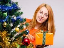 Mooie jonge vrouw die aanbiedend u aanwezige Kerstmis glimlachen. Royalty-vrije Stock Afbeelding