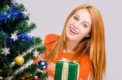 Mooie jonge vrouw die aanbiedend u aanwezige Kerstmis glimlachen. Royalty-vrije Stock Foto's