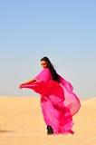 Mooie jonge vrouw die in Arabische woestijn danst Stock Afbeeldingen