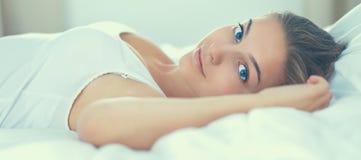 Mooie jonge vrouw die in bed gelukzalig liggen comfortabel en royalty-vrije stock foto's