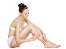 Mooie jonge vrouw die benen ontharen door in de was te zetten royalty-vrije stock foto's