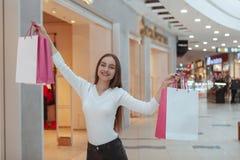 Mooie jonge vrouw die bij de lokale wandelgalerij winkelen stock afbeeldingen