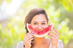 Mooie jonge vrouw die bij park een plak van watermeloen eten stock afbeeldingen