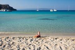 Mooie jonge vrouw die bij schitterend Simos-strand in Griekenland zonnebaden Stock Afbeelding