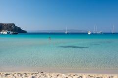 Mooie jonge vrouw die bij schitterend Simos-strand in Griekenland zonnebaden Stock Foto's