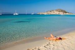 Mooie jonge vrouw die bij schitterend Simos-strand in Griekenland zonnebaden Stock Afbeeldingen