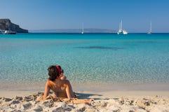 Mooie jonge vrouw die bij schitterend Simos-strand in Griekenland zonnebaden Royalty-vrije Stock Afbeelding