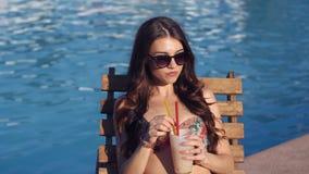 Mooie jonge vrouw die bikini het drinken cocktail dragen, het zitten door de pool en het zonnebaden stock footage