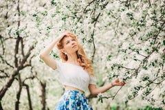 Mooie jonge vrouw die in bloemen maxirok in bloeiende de lentetuin lopen stock fotografie