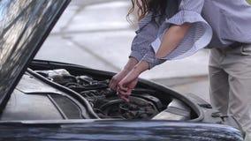 Mooie jonge vrouw die de auto herstellen stock video