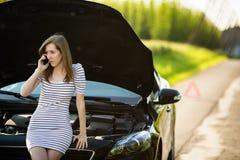 Mooie, jonge vrouw die de de kant van de wegdienst/hulp roepen Stock Foto