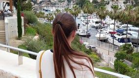 Mooie jonge vrouw die de kleine haven bekijken stock footage
