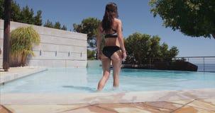 Mooie jonge vrouw die in de pool lopen stock video