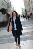 Mooie jonge vrouw die de stad in lopen Stock Foto