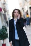 Mooie jonge vrouw die de stad in lopen Stock Afbeelding