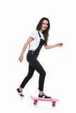 Mooie jonge vrouw die die en bij camera met een skateboard rijden glimlachen op wit wordt geïsoleerd Stock Afbeeldingen