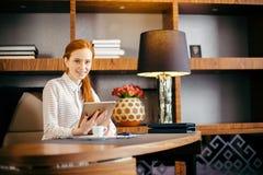 Mooie jonge vrouw die digitale tablet houden en camera met glimlach bekijken Royalty-vrije Stock Afbeeldingen
