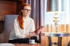 Mooie jonge vrouw die digitale tablet houden en camera met glimlach bekijken Royalty-vrije Stock Fotografie