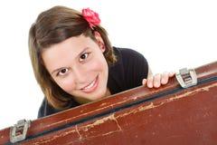 Mooie jonge vrouw die door koffer glimlacht Stock Foto's