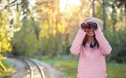 Mooie jonge vrouw die door verrekijkers in de aard kijken stock fotografie