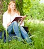 Mooie jonge vrouw die een boek leest Stock Foto's