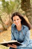 Mooie jonge vrouw die een boek in park lezen bij daling Stock Fotografie
