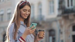 Mooie jonge vrouw die een de functie van de smartphonespraakherkenning online status op de oude stadsstraat gebruiken, die spreke stock video