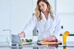 Mooie jonge vrouw die een digitale tablet in de keuken gebruiken royalty-vrije stock foto's