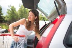 Mooie jonge vrouw die in een een kruidenierswinkelopslag/supermarkt winkelen royalty-vrije stock fotografie
