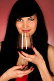 Mooie jonge vrouw die een glas rode wijn houden Stock Foto's