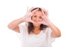 Mooie jonge vrouw die een hart met handen maken stock foto's