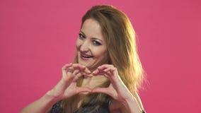Mooie jonge vrouw die die een hart met handen maken, op roze worden geïsoleerd stock videobeelden