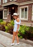 Mooie jonge vrouw die een hoed in het openluchtbinnenplaats plaatsen dragen Stock Fotografie