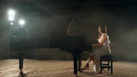 Mooie jonge vrouw die een kleding dragen die pianomuziek op stadium maken 4k lengte stock videobeelden