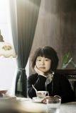 Mooie jonge vrouw die een kop van hete drank houdt Stock Foto's