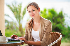 Mooie, jonge vrouw die een laptop computer thuis met behulp van Royalty-vrije Stock Foto's
