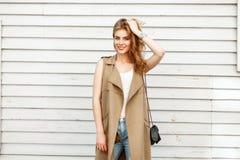 Mooie jonge vrouw die in een modieus vest en jeans glimlachen royalty-vrije stock foto