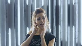 Mooie jonge vrouw die in een nachtclub dansen, die aan muziek door hoofdtelefoons luisteren Snelle energieke dans stock videobeelden