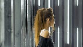 Mooie jonge vrouw die in een nachtclub dansen, die aan muziek door hoofdtelefoons luisteren Zingt een lied voor de camera stock video
