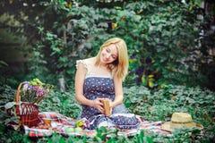 Mooie jonge vrouw die een picknick in het platteland hebben Gelukkige comfortabele dag in openlucht open Glimlachende vrouw met b Royalty-vrije Stock Afbeeldingen