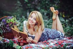 Mooie jonge vrouw die een picknick in het platteland hebben Gelukkige comfortabele dag in openlucht open Glimlachende vrouw met b Royalty-vrije Stock Fotografie