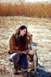 Mooie jonge vrouw die een schor hond koesteren Hoofd-aan-hoofd Stock Foto's