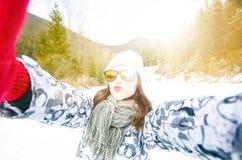 Mooie jonge vrouw die een selfie in de winteraard nemen Mooie vrouw die een foto in een aard nemen De achtergrond van de winter Stock Fotografie