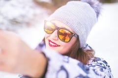 Mooie jonge vrouw die een selfie in de winteraard nemen Mooie vrouw die een foto in een aard nemen De achtergrond van de winter Stock Afbeelding