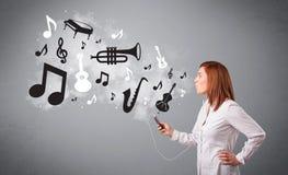 Mooie jonge vrouw die en aan muziek met musica zingen luisteren Stock Afbeelding