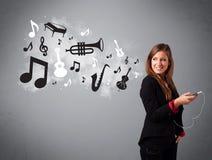Mooie jonge vrouw die en aan muziek met musica zingen luisteren Royalty-vrije Stock Foto