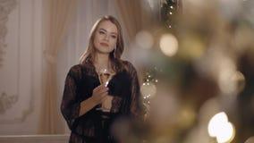 Mooie jonge vrouw die en zich op Kerstmisachtergrond bevinden stellen stock video