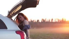 Mooie jonge vrouw die gelukkig en in de boomstam van een auto tijdens een wegreis dansen in Europa in de laatste notulen van Goud stock videobeelden