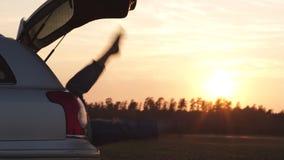 Mooie jonge vrouw die gelukkig en in de boomstam van een auto tijdens een wegreis dansen in Europa in de laatste notulen van Goud stock footage